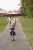 Girl cycling with siblings on road amidst grassy field at park