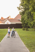 Friends with skateboard and bicycle at park against houses
