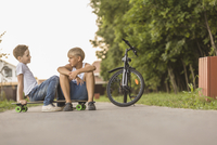 Friends talking while sitting on skateboard by bicycle at park