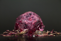 Close-up of beet with peel on table against black background