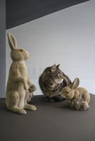Tabby cat looking away while sitting by rabbit figurines on floor against wall 11016034584| 写真素材・ストックフォト・画像・イラスト素材|アマナイメージズ