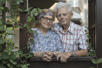 Portrait of smiling senior couple standing at window
