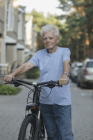 Portrait of senior adult standing with bicycle on city street