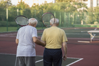 Rear view of senior friends carrying tennis rackets while walking at playing field