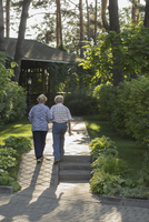 Rear view of couple walking towards house amidst plants