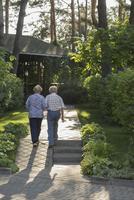 Rear view of couple walking towards house amidst plants 11016034592| 写真素材・ストックフォト・画像・イラスト素材|アマナイメージズ