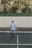 Senior man playing tennis against wall at playing field