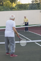 Senior men playing tennis at court