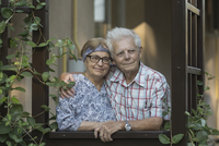 Thoughtful smiling senior couple standing at window