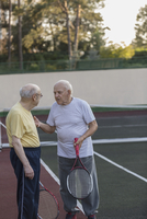 Senior friends talking while holding tennis rackets at court
