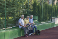 Senior friends with tennis rackets sitting against fence at court