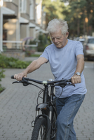 Senior man cycling on cobbled street in city