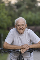 Portrait of senior man leaning on bicycle at park
