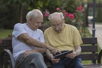 Senior man pointing and showing to friend at park bench 11016034626| 写真素材・ストックフォト・画像・イラスト素材|アマナイメージズ