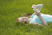 Young woman using phone while lying on grassy field