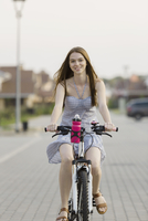 Portrait of smiling woman cycling on cobbled street in city