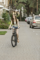 Smiling woman cycling on cobbled street against parked cars in city