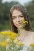 Portrait of beautiful woman with yellow flowers at park