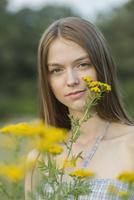 Portrait of beautiful woman with yellow flowers at park 11016034650| 写真素材・ストックフォト・画像・イラスト素材|アマナイメージズ