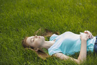 Young woman resting with eyes closed on grassy field