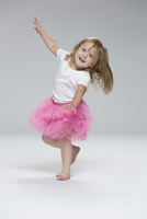 Cute girl wearing tutu dancing against gray background