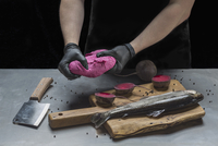 Midsection of man kneading pink dough over raw fish and beetroots at table