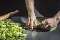 Midsection of man kneading green dough by basils at table