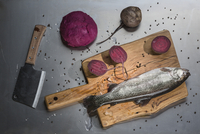 Directly above shot of raw fish and beetroots with knife at table