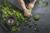 Cropped image of hands kneading green dough by basil ice cubes at table