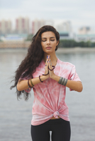 Young woman with closed eyes practicing yoga in prayer position against river 11016034681| 写真素材・ストックフォト・画像・イラスト素材|アマナイメージズ