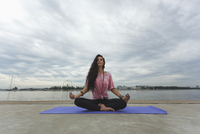 Woman meditating in lotus position at riverbank against cloudy sky 11016034683| 写真素材・ストックフォト・画像・イラスト素材|アマナイメージズ