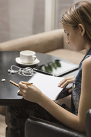 Young woman studying while having coffee at library