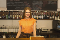 Portrait of smiling woman standing at bar counter