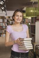 Portrait of smiling student carrying stack of books at library