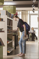 Side view of woman searching for book at library