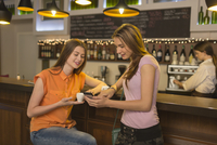 Woman showing phone to friend at counter with bartender in background