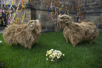 Sheep made from hay on grass against stone wall