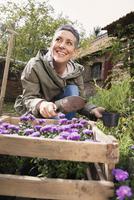 Happy woman planting flowers in back yard 11016034710| 写真素材・ストックフォト・画像・イラスト素材|アマナイメージズ