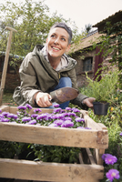 Happy woman planting flowers in back yard