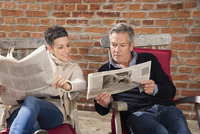 Man showing newspaper to woman while sitting in back yard