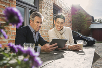 Mature couple sitting with digital tablet and coffee in back yard
