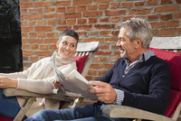 Happy woman looking at man holding newspaper while sitting in back yard