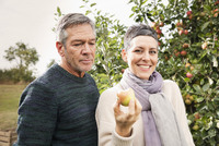 Portrait of happy woman holding apple by man in orchard
