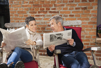 Man showing newspaper to happy woman while sitting in back yard 11016034726| 写真素材・ストックフォト・画像・イラスト素材|アマナイメージズ