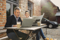 Mature man using laptop with woman holding newspaper in back yard