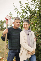 Portrait of happy woman standing with man in apple orchard 11016034738| 写真素材・ストックフォト・画像・イラスト素材|アマナイメージズ