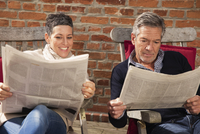Happy couple reading newspaper against brick wall in back yard