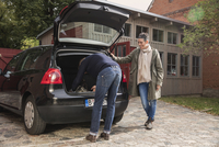 Woman watching man packing luggage in trunk 11016034744| 写真素材・ストックフォト・画像・イラスト素材|アマナイメージズ