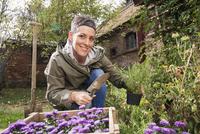 Portrait of happy woman gardening in back yard