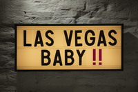 Close-up of Las Vegas Baby signboard against gray wall